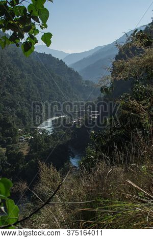 Marshyangdi River Flowing Through A Valley Close To A Mounatin Village At Annapurna Circuit, Nepal