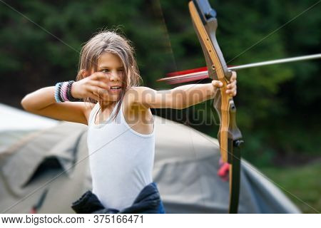 Padis, Bihor County, Romania - August.25.2016: Happy Girl Shooting With A Bow And Arrow In A Forest