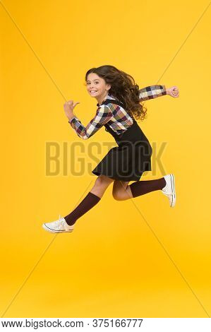 Break Into. Feel Inner Energy. Girl With Long Hair Jumping On Yellow Background. Carefree Kid Summer