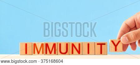 Immunity Concept. Man Stacks Wooden Blocks With The Inscription Immunity