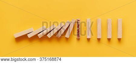 Immunity Concept. Falling Wooden Blocks Rest Against A Block Labeled Immunity