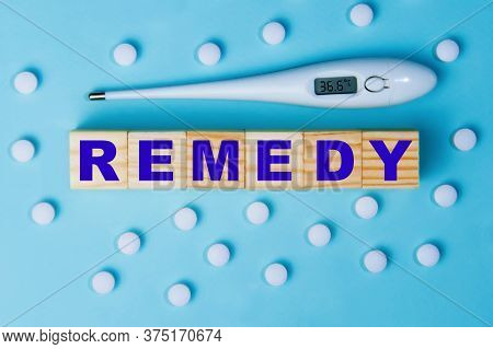 The Word Remedy On Wooden Cubes With Pills And A Thermometer On A Blue Background.