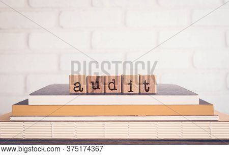 The Word Audit, Alphabets On Wooden Rubber Stamps On Top Of Books With Bricks Background, Blank Copy
