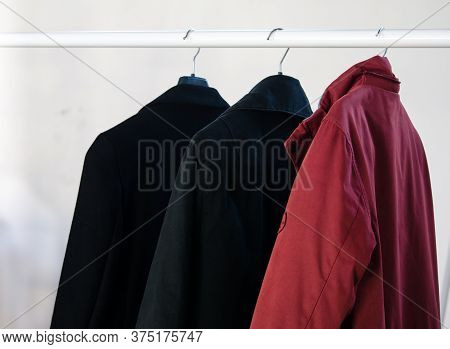Three Coats Hanging On A Coat Rack. Winter Clothes Isolated On White Background. Laundry, Dry Cleani