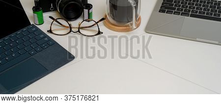 Cropped Shot Of Copy Space On Modern Home Worktable With Laptop, Tablet With Keyboard, Glasses And C