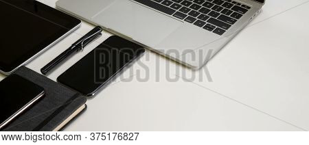 Modern Office Desk With Digital Devices, Pen, Schedule Book And Copy Space On White Table