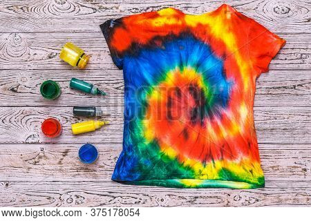 The Back Of A Tie Dye T-shirt On A Wooden Table With Paint. White Clothes Painted By Hand. Flat Lay.