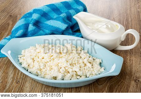 Striped Napkin, Gravy Boat With Sour Cream, Grainy Cottage Cheese In Blue Oval Bowl On Wooden Table
