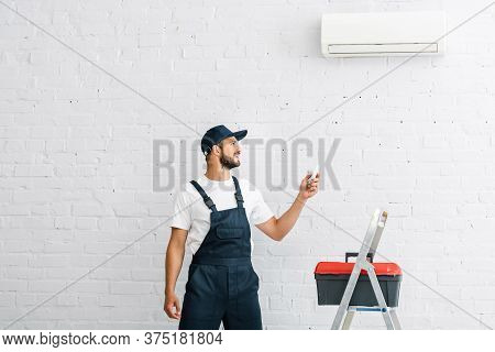 Workman Switching Air Conditioner With Remote Controller Near Toolbox On Ladder