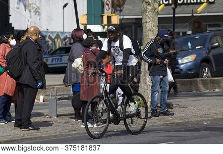 Bronx, New York/usa - May 20, 2020: Man Rides Bike Without Mask While Others Wait For Bus Wearing On