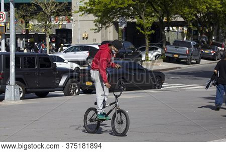 Bronx, New York/usa - May 20, 2020: African American Male Wears Face Mask On Bike While Using Phone