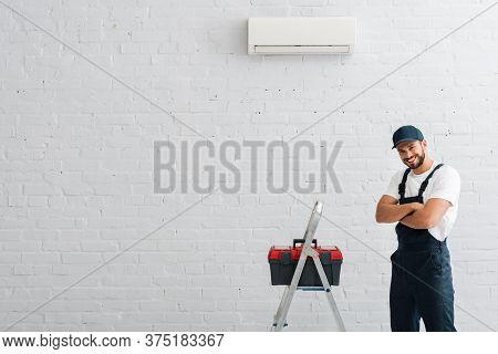 Workman With Crossed Arms Looking At Camera Near Toolbox On Ladder And Air Conditioner On Wall