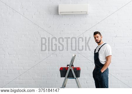 Workman With Hands In Pockets Of Overalls Looking At Camera Near Toolbox On Ladder And Air Condition