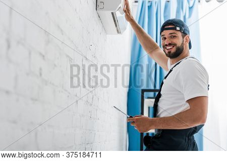 Workman Looking At Camera While Repairing Air Conditioner