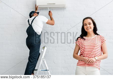 Focus Of Smiling Woman Looking At Camera While Workman Fixing Air Conditioner