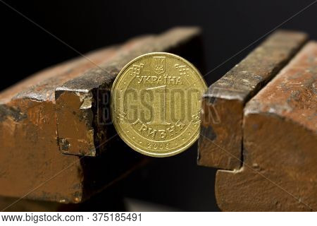 A Coin In A Metal Vise. Hryvnia In A Vise. Concept Of Economic Problems. Selective Focus. Close Up