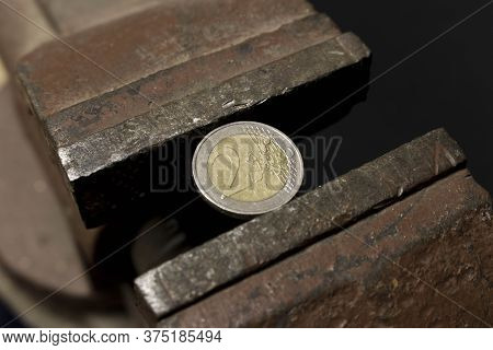 2 Euro Coin In A Metal Vise. Concept Of Economic Problems. Selective Focus. Close Up