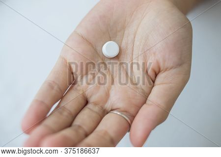 Hand Holding Pill, Taking Medicine On Bed In Morning At Home. Migraine, Painkiller, Headache, Influe