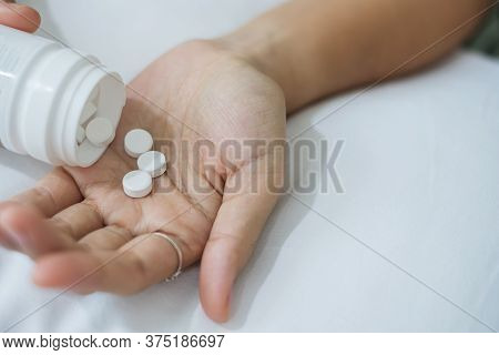 Adult Woman Pours The Pills From Bottle, Taking Medicine On Bed In Morning At Home. Migraine, Painki