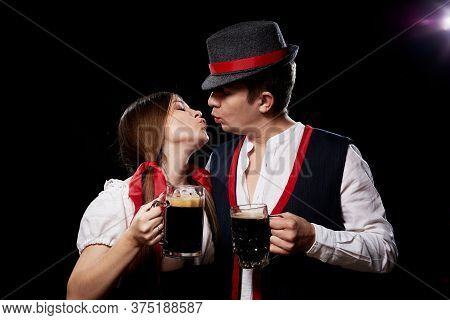 Happy Oktoberfest Couple In National Ethnic Dress Clinking Beer Mugs And Kissing Each Other On A Bla