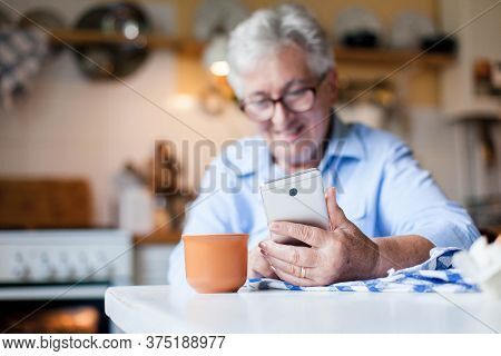 Senior Woman Using Mobile Phone At Home Kitchen. Happy Retired Person Shopping Online. People Virtua