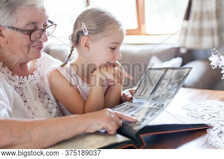 Happy Family Watching Old Photo Album At Home Together. Senior Woman Showing Child Black And White V