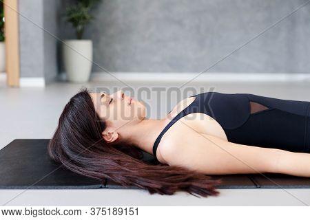 Young Woman Practicing Hatha Yoga At Home. Girl Doing Morning Exercises. Shavasana Or Savasana In Co