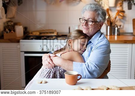 Senior Woman Hugging Child At Home. Happy Family Enjoying Kindness, Support, Care Together In Cozy K
