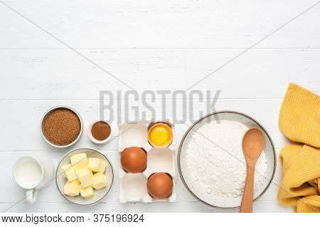 Baking Ingredients On White Wooden Table. Ingredients For Baking Pastry Cake Or Cookies. Bowl Of Whe