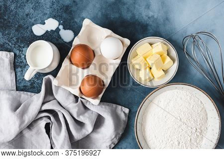 Ingredients For Baking On Blue Background. Eggs, Cubed Butter, Milk Flour And Whisker. Top View