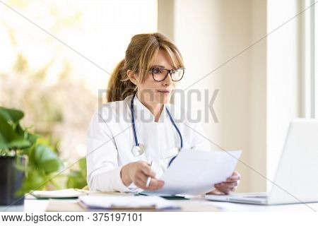 Smiling Female Doctor Sitting At Desk And Working On Laptop