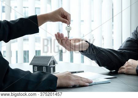 Real Estate Agent Broker Hand Over The House Key To The New Owner After Completing The Signing Accor