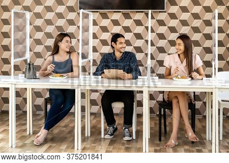 Asian group of friend eating out together at new normal social distance restaurant with table shield partition reduce infection of coronavirus covid-19 pandemic. Restaurant new normal lifestyle.