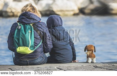 Two People Sitting Back To Back,two People Sitting Back To Back In Front Of The Lake