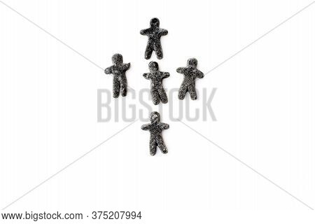 Black Licorice Jelly Figurines Of People Are Arranged In The Form Of A Cross. Conceptual Image.