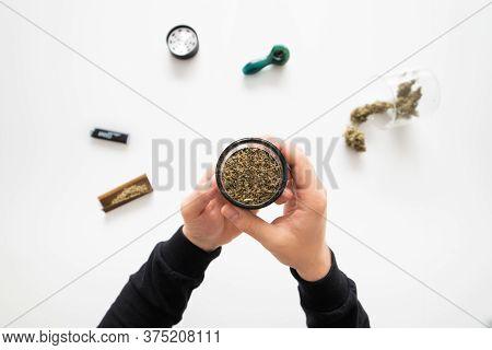 Mans Hands Marijuana Bud. The Sugar Pot Leaves On Buds. Marijuana Nature. Cannabis Buds In Grinder.