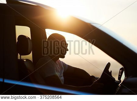 Silhouette Of A Young Man Sitting In His Car, Wearing Sunglasses And Looking At The Sunset, Hand On