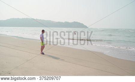 Traveling Young Man Walking Along Sea Coast. Male Tourist Promenading While Resting On Sandy Beach N