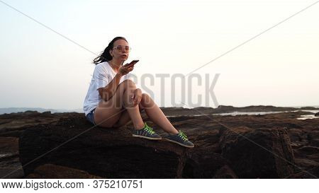 Relaxed Woman Sitting On Stone And Recording Audio Message On Smartphone On Shore. Side View Of Plea
