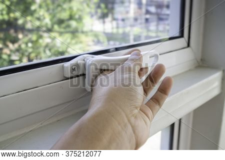 Hand Holding Glass Window Latch Lever, Stock Photo