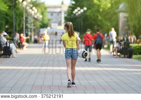 Girl Child Carries Her Discharged Hoverboard In A Public Park, Authentic Photo