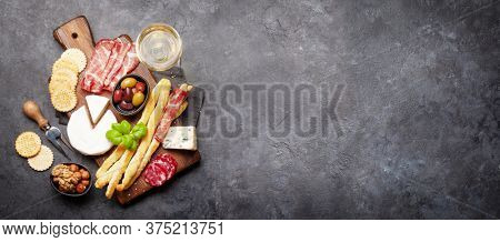 Cheese, meat and olives antipasto. Appetizer selection board and glass with white wine. Top view with copy space. Flat lay wide backdrop