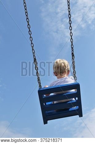 A Boy With Cochlear Implants Riding Swing In Summer Park