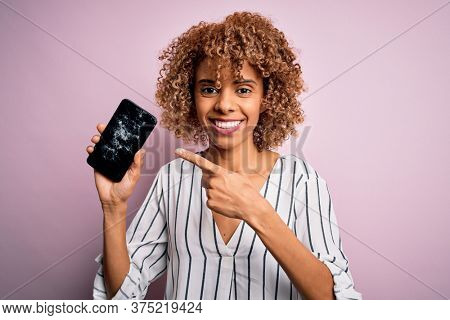 Young african american curly woman holding broken smartphone showing craked screen very happy pointing with hand and finger