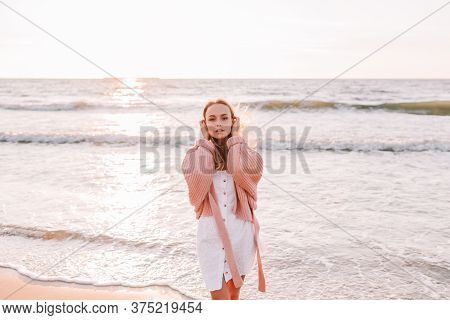 A Young Slender Girl Stands Alone On The Beach Or Ocean And Look At The Camera. A Woman Dressed In A