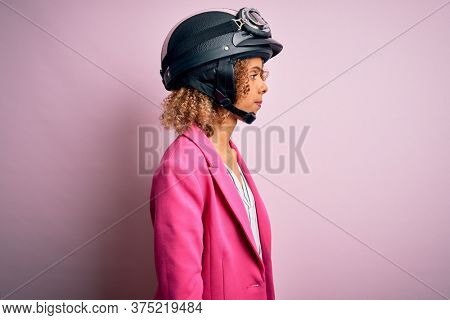 African american motorcyclist woman with curly hair wearing moto helmet over pink background looking to side, relax profile pose with natural face with confident smile.