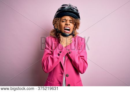 African american motorcyclist woman with curly hair wearing moto helmet over pink background shouting and suffocate because painful strangle. Health problem. Asphyxiate and suicide concept.
