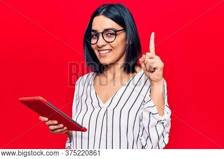 Young beautiful latin woman holding touchpad surprised with an idea or question pointing finger with happy face, number one