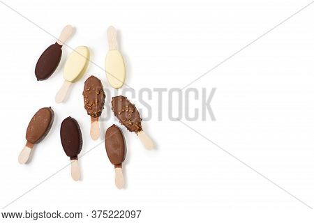 Four Assorted Tipes Of Chocolate Dipped Ice Lollies On A White Background