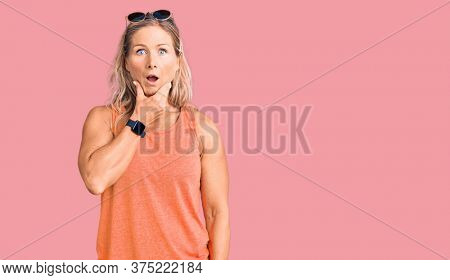 Middle age fit blonde woman wearing casual summer clothes and sunglasses looking fascinated with disbelief, surprise and amazed expression with hands on chin